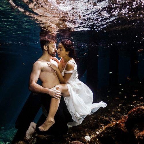 Bride and groom with groom shirt off underwater in Mayan Cenote Trash the Dress, Mexico