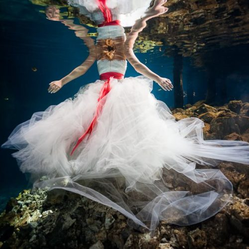 Back of dress with bride underwater in cenote in Meico