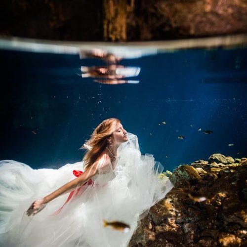 Bride underwater in wedding dress in Riviera Maya