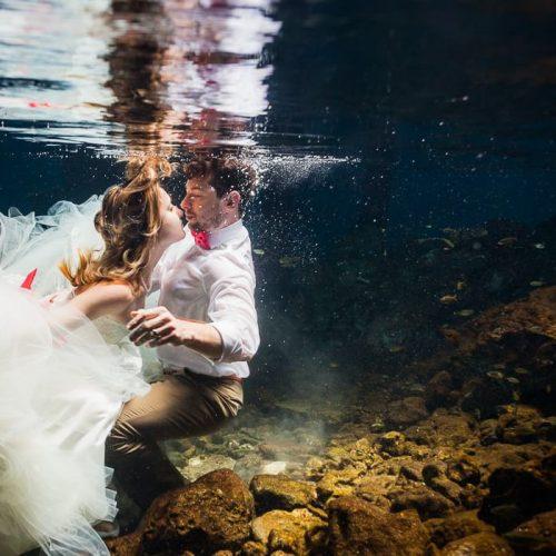 Bride underwater in wedding dress in Mayan Cenote Mexico