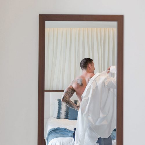 Groom putting on shirt in mirror at Secrets on the vine Cancun
