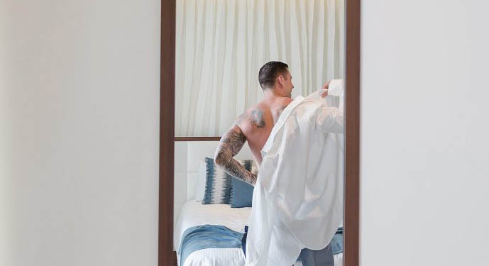 Groom putting on shirt in hotel room before wedding.