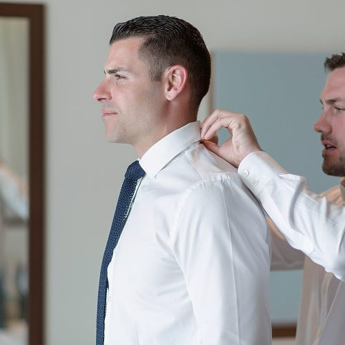 Best man helping groom with shirt collar