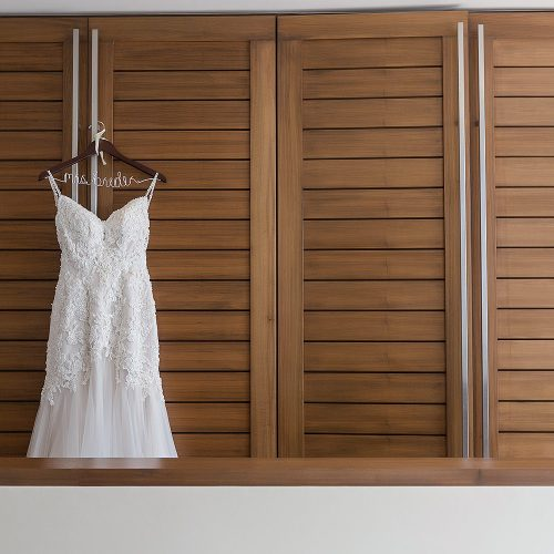 Brides wedding dress hanging in room at Secrets on the vine Cancun