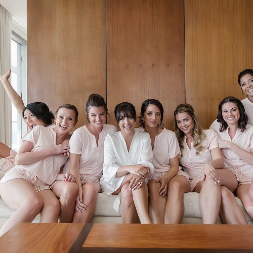 Bride and bridesmaids having fun on sofa at Secrets on the vine Cancun