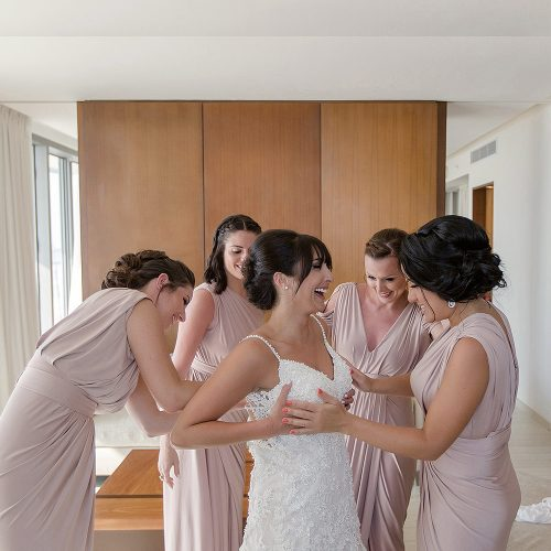 Bride getting dress on with bridesmaids.