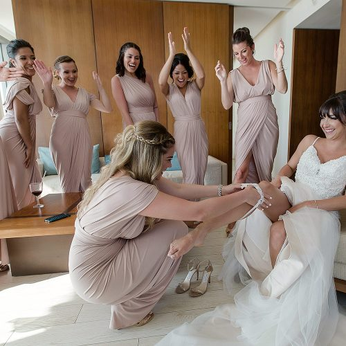 Bridesmaid putting on garter before wedding