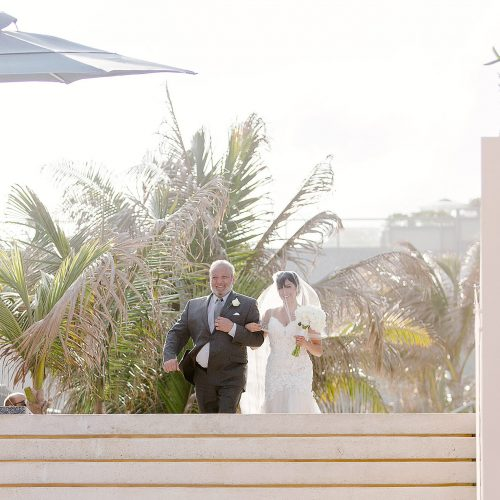 Bride walking to wedding ceremony on beach at Secrets on the vine Cancun