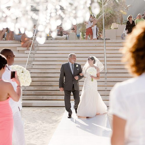 Bride walking down aisle at Secrets on the vine Cancun beach wedding ceremony