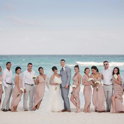 Bride, groom and wedding party on beach in Cancun.