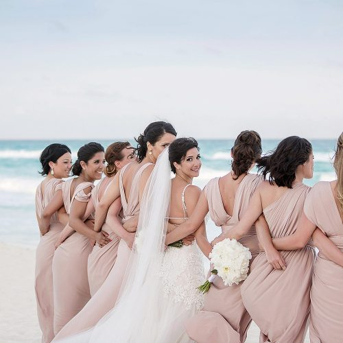 Bride with bridesmaids on beach in Cancun