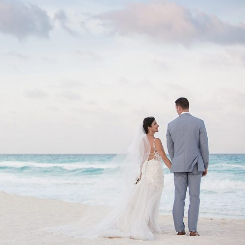 Bride and groom looking away on beach in Cancun