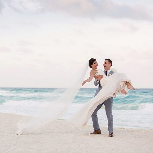 Groom carrying bride on beach in Cancun