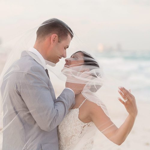 Bride and groom kissing under veil on beach in Cancun