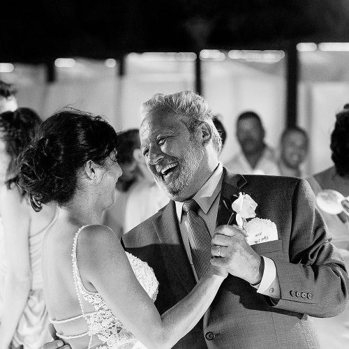 Bride and father laughing during father daughter dance.