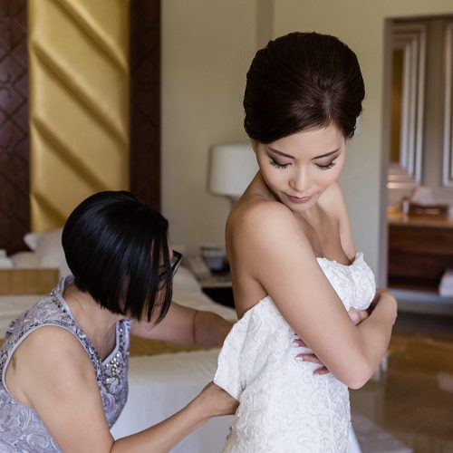 Bride and mother putting on wedding dress in room at Moon Palace Cancun