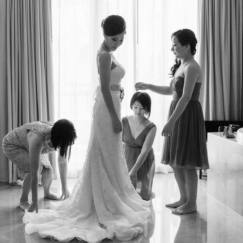 Bridesmaids helping bride with dress at Moon Palace Cancun