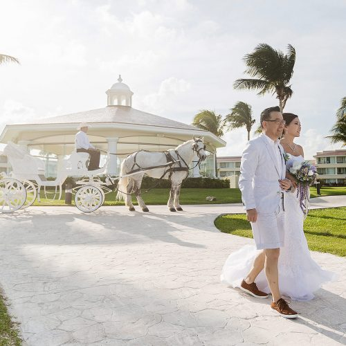 Bride walking away with horse and carriage in background at Moon Palace Cancun