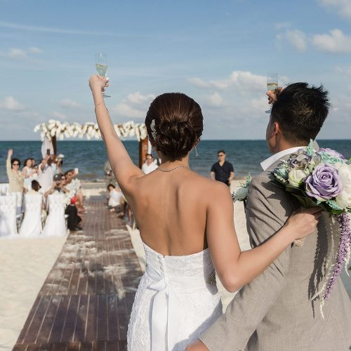 Bride and groom saluting guests at wedding ceremony on beach in Cancun