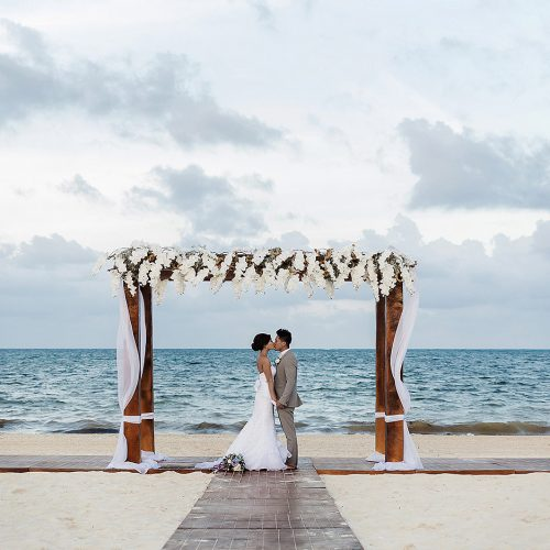 Bride and groom under alter at Moon Palace Cancun beach ceremony
