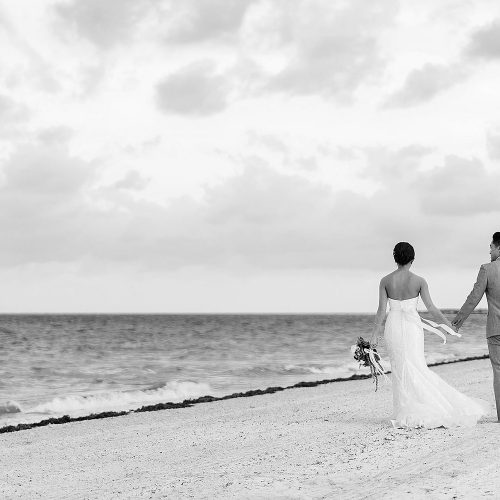 Bride and groom walking down beach holding hands in Cancun