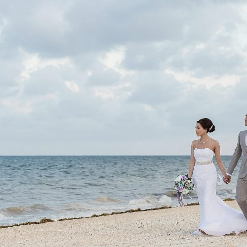 Bride and groom walking and holding hands on beach in Cancun