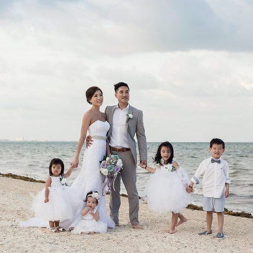 Bride and groom with flower girls and ring bearer on beach in Cancn