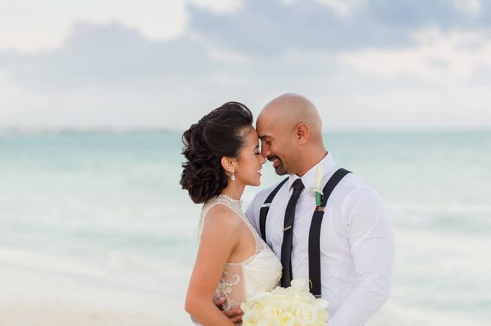 Bride and groom facing each other on beach in Cancun at sunset