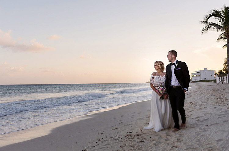 Bride and groom walking on beach in Cancun at sunset