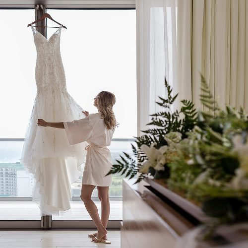 Bride looking at dress in room at Secrets on the Vine in Cancun