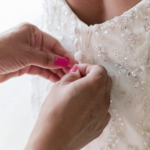 Close up of mother doing up brides wedding dress