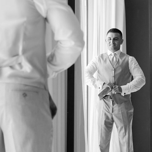 Groom looking in mirror getting ready at Secrets on the Vine in Cancun