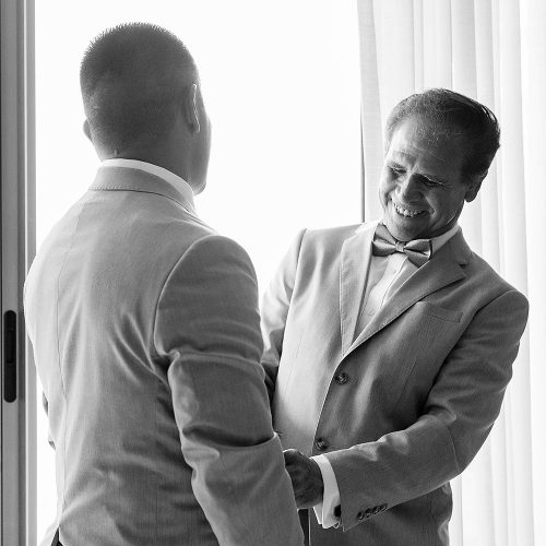 Father helping groom get ready before wedding.