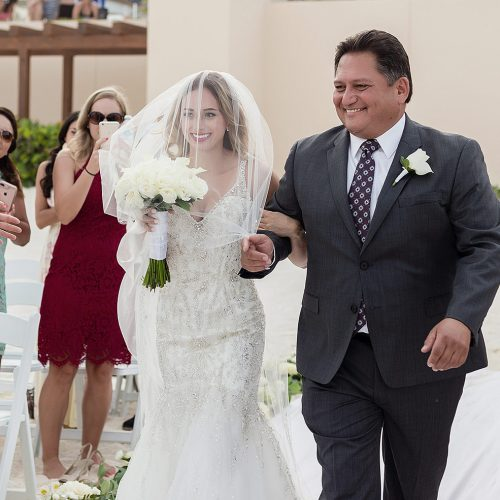 Bride walking down aisle on beach in Cancun