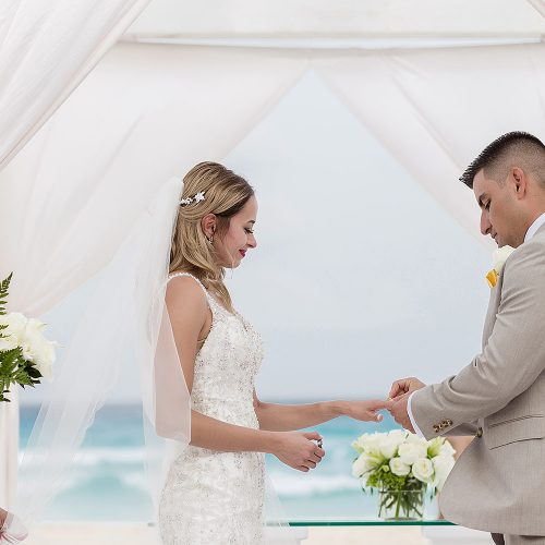 Bride and groom at wedding ceremony on beach at Secrets on the Vine in Cancun
