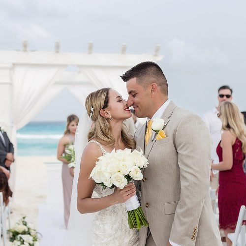 Bride and groom kissing after wedding ceremony on beach in Cancun