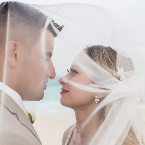 Bride and groom under veil on beach in Cancun