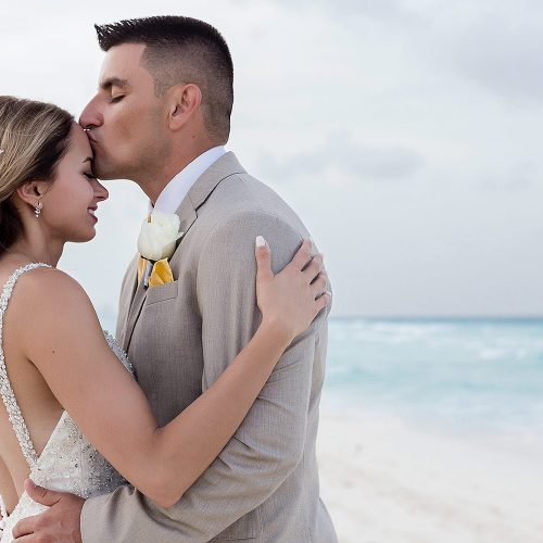 Groom kissing brides forehead on beach in Cancun