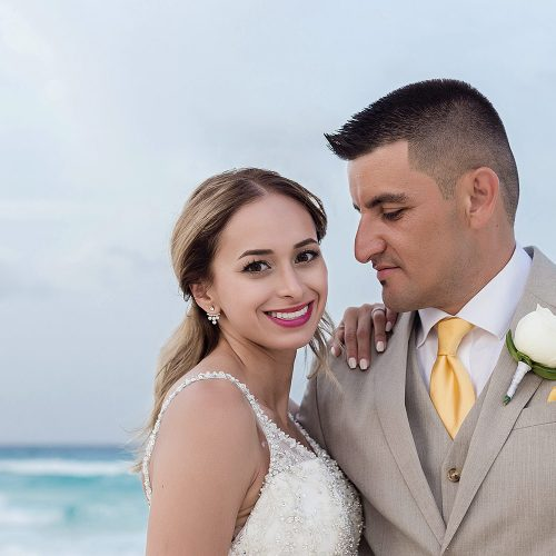 Groom looking at bride on beach in Cancun