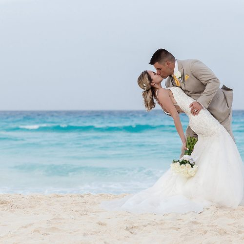 Groom dipping bride on beach in Cancun.