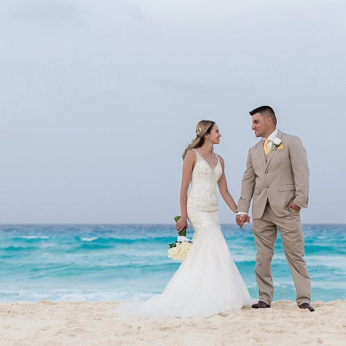 Bride and groom holding hands on beach in Cancun
