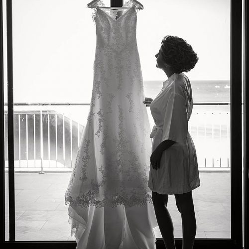 Bride standing at window looking at wedding dress in Playa del Carmen