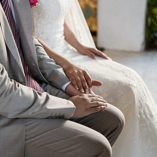Close up of bride and groom holding hands at wedding ceremony in Riviera Maya