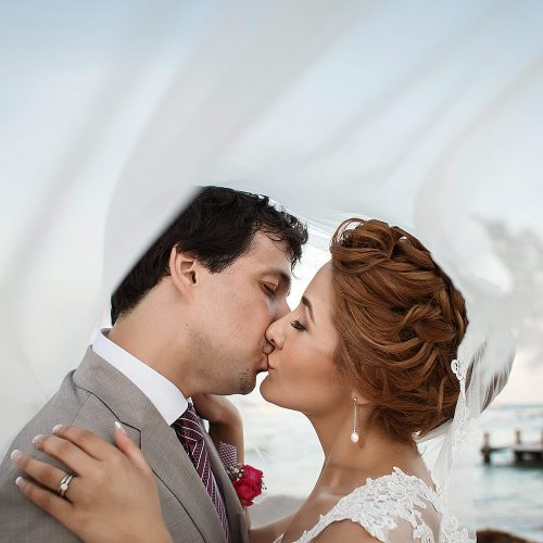 Bride and groom kissing under veil.