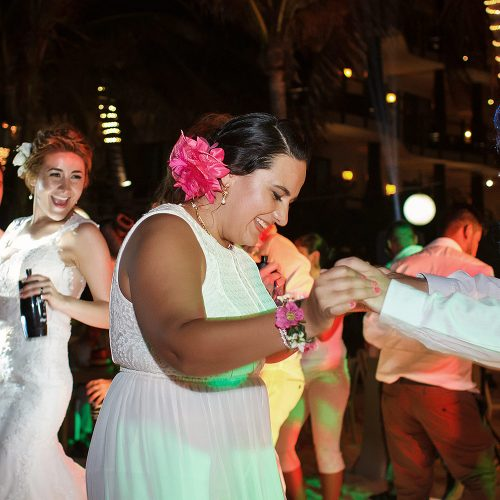 Guests dancing on dance floor at wedding