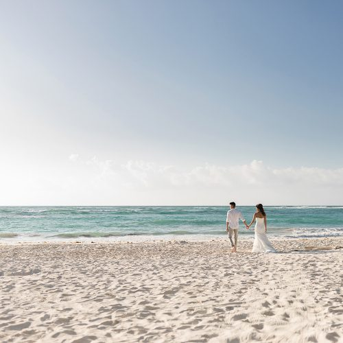 Bride and groom walking on beach in Riveira Maya Mexico