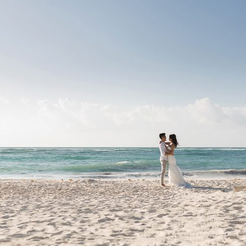 Bride and groom kissing on beach in Riveira Maya Mexico