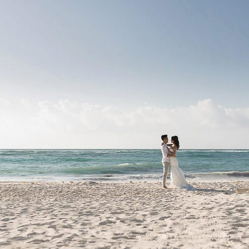 Bride and Groom kissing on beach in Riviera Maya