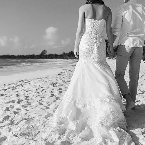 Bride and groom holding hands walking away on beach