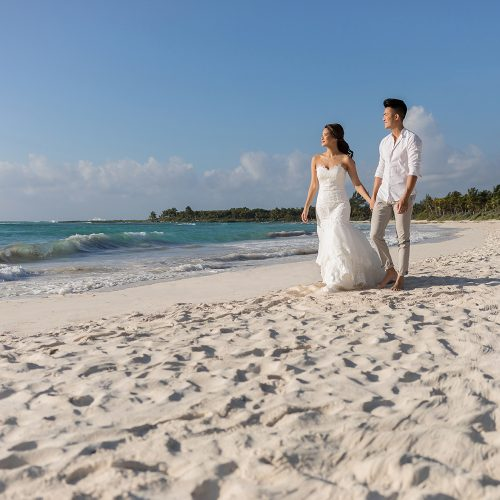 Bride and groom walking and holding hands on beach in Riviera Maya Mexico